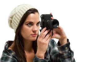 ung kvinna med brunt hår håller kameran foto