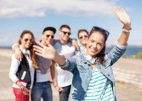 tonårsflicka med hörlurar och vänner utanför foto