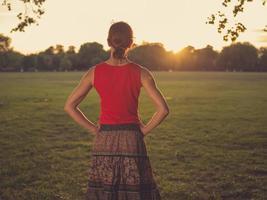 kvinna som står i park och beundrar solnedgången foto
