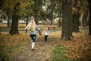 mamma med dotter i höst park foto