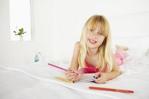 ganska ung flicka som ligger på sängen foto