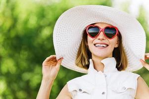 porträtt ung charmig kvinna vit hatt röda solglasögon foto