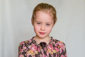 lugn förskoleflicka med jordgubbblonde hårstrån och blommig klänning foto