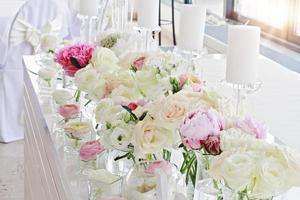 bröllop bord dekoration. ranunculus, rosor, ljus foto