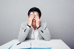 ung asiatisk affärsman som gnuggar ögonen foto