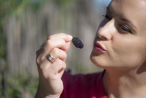 vacker kvinna äter en svart mullbär foto