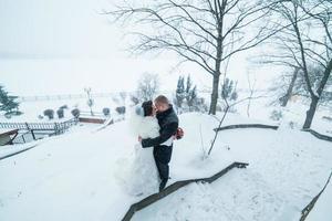 bruden och brudgummen som går i snön foto