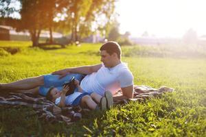 pappa och son som vilar i parken på gräset foto