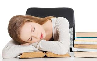 vacker kvinna sover på en bok. foto