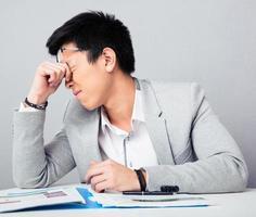 trött affärsman som sitter vid bordet foto