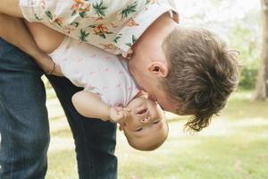 far som spelar sin söta baby utomhus i vårparken foto