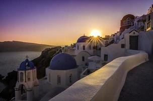 solnedgång utsikt över de blå kupolkyrkorna i santorini, Grekland foto