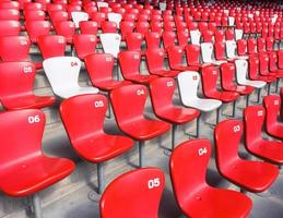 röda stolar blekare i stora stadion foto