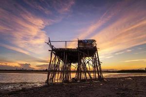 överge träfiskarstuga i vacker solnedgångsscene