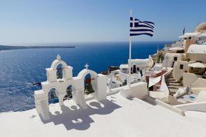 grekisk flagga med översikt över oia, santorini foto