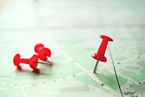 tre röda markeringsstift ovanpå en karta foto