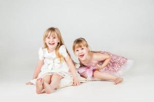 två små modeflickor i vacker klänning foto