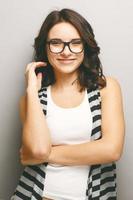 stående attraktiv kvinna på grå bakgrund. foto