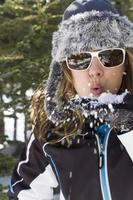 kvinna som blåser snö foto