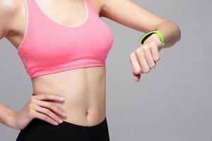 sportkvinna som kontrollerar sin smarta klocka foto