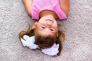 liten flicka som ligger på golvet. foto