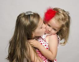 ung flicka som håller sin lilla syster i armarna. foto
