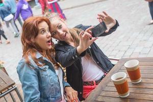 flickor tar bilder med mobiltelefon foto