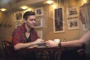 par har ett datum på café. de dricker kaffe foto