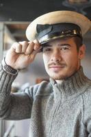 attraktiv ung man som bär armé marin gammal hatt foto