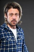 uttrycksfull ung man med blont långt hår och skägg. foto