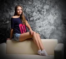 ung flicka sitter på soffan foto
