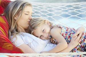 mor och dotter kopplar av i trädgårdshängmatta foto