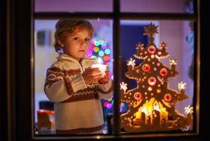 lyckligt litet barn som står vid fönstret vid jultid foto