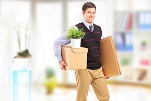 leende ung man med lådor flyttar i en lägenhet foto