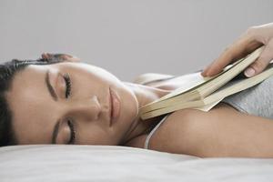 vacker kvinna håller boken medan du sover i sängen foto
