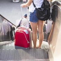ung flicka med den röda resväskan som står på rulltrappan. foto