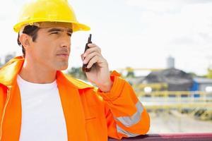 manlig byggnadsarbetare som kommunicerar på walkie-talkie på plats foto
