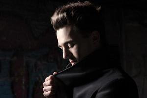 urban mode ung man med femtiotal frisyr klädd i svart. foto