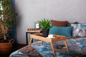 sovrum inredning med ett litet bord på sängen