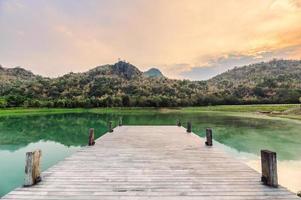träbrygga vid sjön vid solnedgången foto