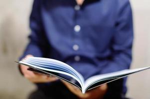 en affärsman i en blå skjorta med öppen anteckningsbok