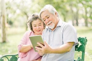 äldre asiatiska par använder surfplatta i parken foto