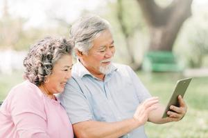 äldre par som använder surfplattan utomhus foto