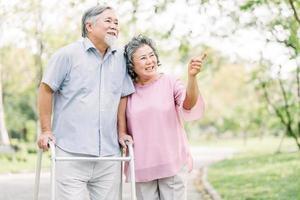 lyckliga äldre par som går med vandrare i en park foto