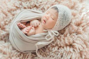 nyfött baby wrapprd i kokong sova på päls foto