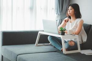 kvinna som arbetar hemifrån på soffan foto