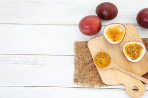 färska passionfrukter på vitt träbord med skärbräda foto