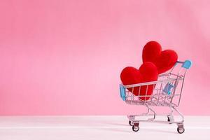 rött hjärta formar i kundvagn på rosa bakgrund