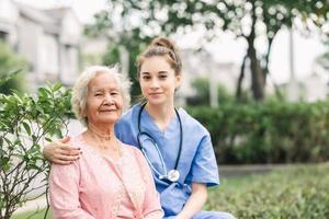 vårdgivare som omfamnar senior i parken foto