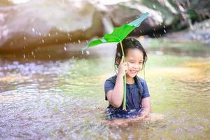 liten asiatisk flicka som leker i vatten foto